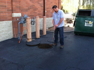 Tempe's Jeff Vebber checks a grease trap outside a downtown restaurant.